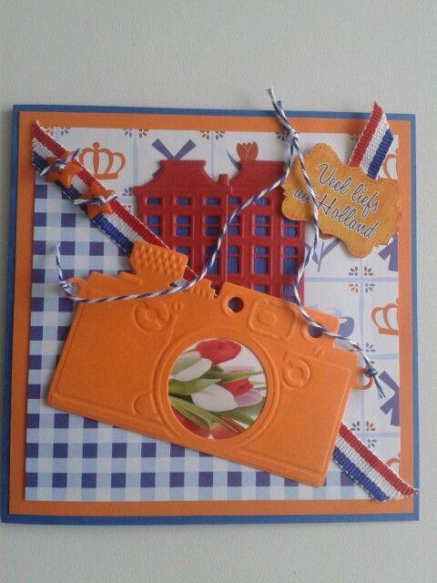 Kaart van holland in rood.wit.blauw met oranje fototoestel. Grachtenpandjes en in de lens...TULPEN...