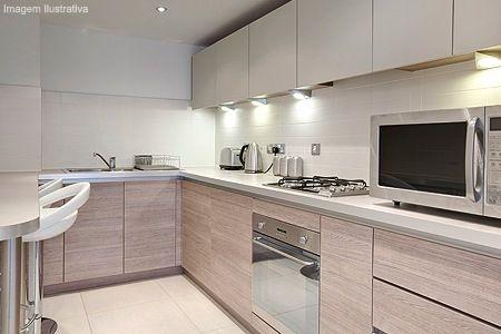 Cozinha com bancada branca, madeira clara (ciliegio).