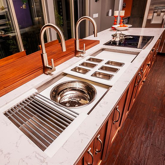 Make It Multitask | The Galley Sink doubles as a work zone through a series of integrated cutting surfaces, colanders, bowls and racks. We added two sleek STo pull-down faucets from Moen.