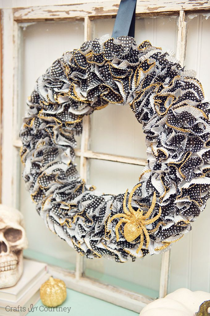 This Halloween wreath is so easy to make - it only takes about 30 minutes! Grab your cupcake liners, glitter, and Mod Podge. So festive!