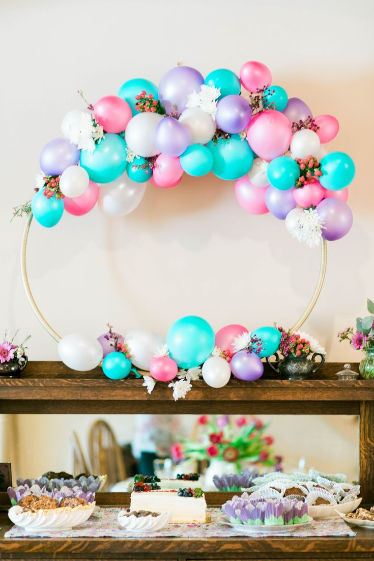 A floral, balloon wreath for the centerpiece of a baby shower in Houston, Texas! Made with a hula hoop, spray paint, low-temp hot glue, balloons, and on-sale filler flowers.