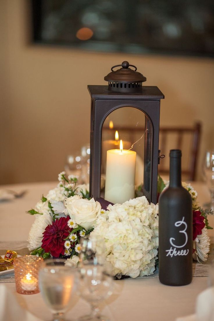 I like the wine bottle idea! Paint wine bottle with chalk paint and write  table number. Cute and inexpensive. With pink flowers instead of the red  ones