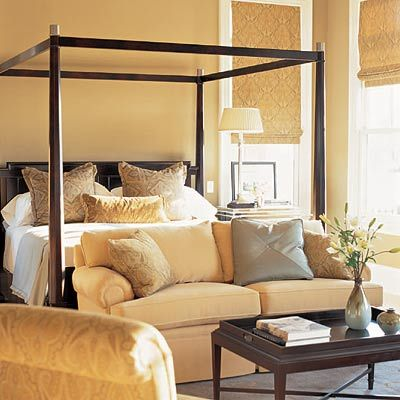 Master bedroom with black canopy bed and small sitting area    Love the bamboo roman shades and wood tray coffee table! Gold yellow paint wall color! gold yellow brown blue green bedroom colors!