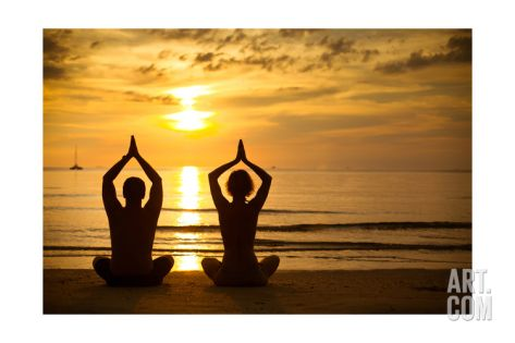 Young Couple Practicing Yoga On The Sea Beach At Sunset Art Print by De Visu at Art.com