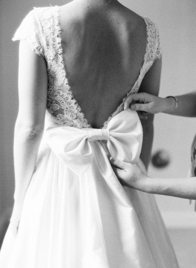 Gorgeous classic lace dress with a satin bow: http://www.stylemepretty.com/north-carolina-weddings/charlotte/2016/02/02/classic-elegant-north-carolina-country-club-wedding/ | Photography: Allison Kuhn - http://www.allisonkuhnphotography.com/