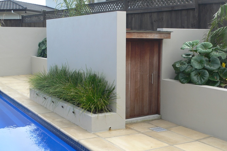 Pool shed built into garden with the door hidden from the main entertainment areas. The front is a water feature with the wall set up as an outdoor projection screen to watch movies etc. Design & soft landscaping by Fusion Landscape Design Ltd. www.fusionlandscapedesign.co.nz
