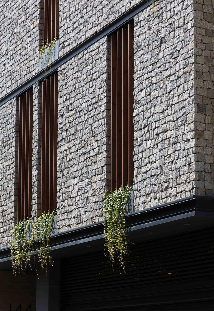 O design vertical das janelas com uma profundidade de 70 cm com instalação de persianas de madeira verticais, reduzem a intensidade da luz solar direta nos dormitórios ao leste. Assim, um espaço verde para cada dormitório parecia satisfazer os moradores da necessidade de se conectar com a natureza e proporcionar uma sensação de vitalidade em cada espaço (dormitório) e também trazer uma visão interessante para os transeuntes. #edifício #wall #fachada #facade #plantas #building #arquitetura