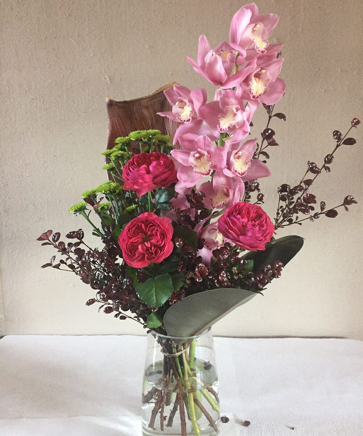 A breathtaking combination of fresh beautiful classique roses, cymbidium orchids, button chrysanthemum, myrtle and trop top. Order online today at:  https://jaclynroma.com/shop/product/the-anniversary-flower-bouquet/