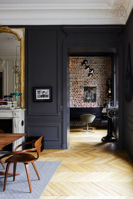 Modern glamour in a Parisian apartment painted a dark charcoal gray and accented with gilded mirrors and modern furniture,