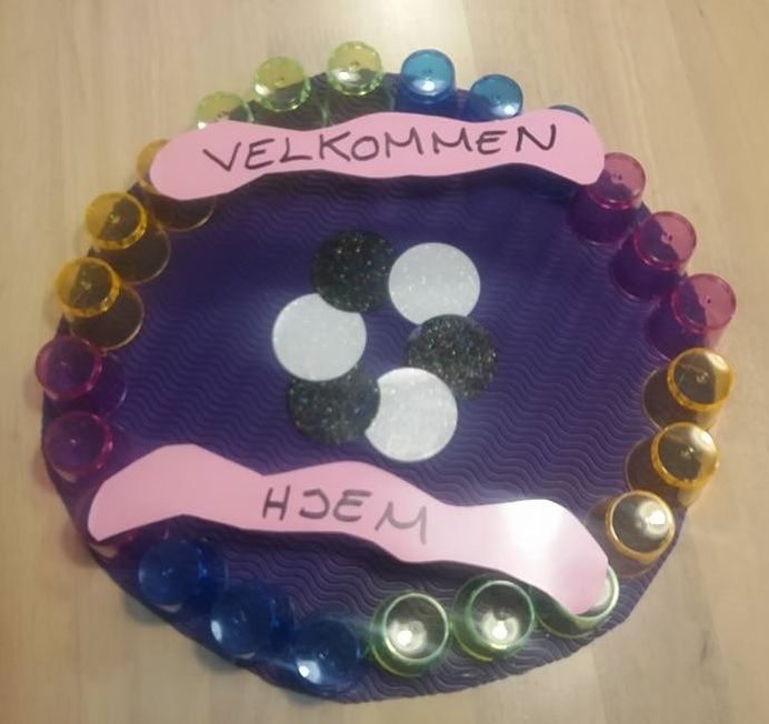 A welcome home sign. Plastic shotglasses glued on cardboard, cardboard with the…