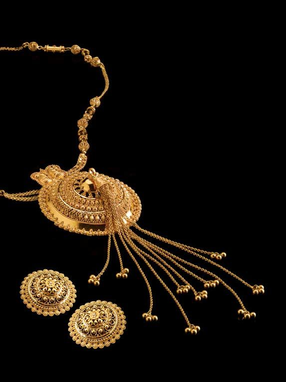 Dhakai Pasha Pendant  Huge earrings, like plaques, were popular in undivided Bengal and the fashionable ladies of Dhaka sported a variety. Now revived as a storied but light katai-work pendant on a detachable ornamental chain, the Dhakai Pasha comes with a slightly diminutive and deliberately mismatched pair of earrings, lending the ensemble an impromptu charm ; not in the least out of place at a club soiree, and just as graceful at a posh biyer bari. All in pure 22K yellow gold.