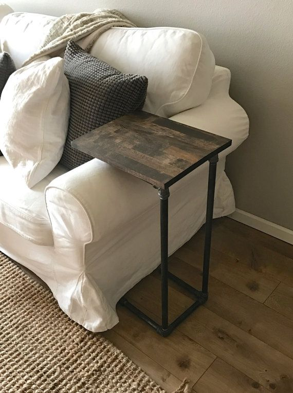 Check out this industrial styled side table! Perfect for setting drinks, food, laptops, or anything else right next to you. Its sleek industrial style will look great in your living room. The top is made from aspen butcher block: sanded and stained for a smooth finish. The legs and base are steel pipe. Designed to fit over couch cushions and side rests, the legs have 24 clearance. The top measures 12 by 15. Three stain colors are available: dark oak, early American, and natural.