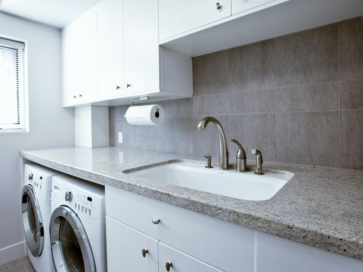 Granite countertops, a utility sink and simple white cabinets make this Scandinavian laundry room chic and functional. Laundry day is made easier with a perfectly positioned folding counter over the washer and dryer and plenty of storage space.