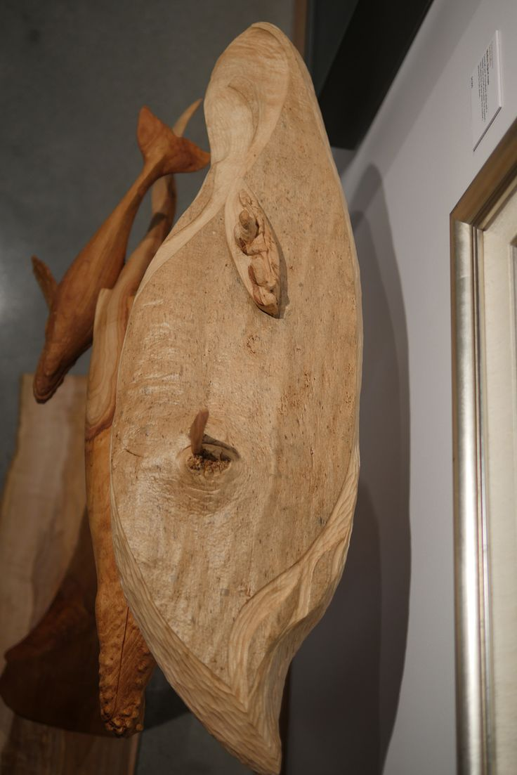 'Convergence', Bigleaf Maple, 110 cm x 110 cm x 40 cm. Part of the oneTree Exhibit at the Robert Bateman Centre in Victoria, BC, Canada.  Carved from one branch of a Bigleaf Maple tree, it depicts a cow-calf pair of humpback whales as they glide underneath a kayak. The mother's pectoral fin breaches the surface giving the person in the kayak a brief glimpse of the enormous and beautiful animals underneath.
