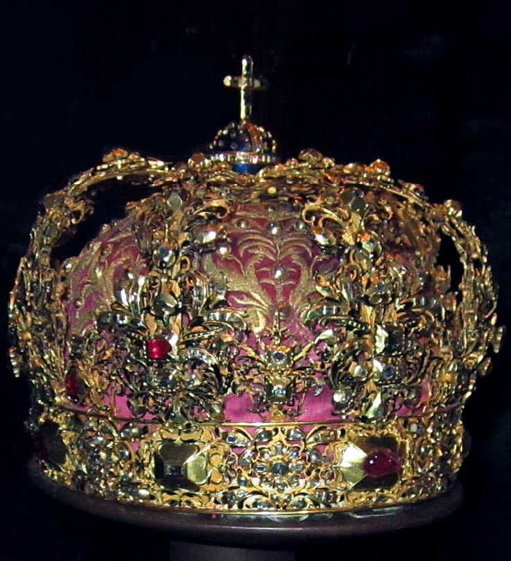Crown of Queen Christina, made for her mother. As her coronation and state crown Christina of Sweden used the crown that her mother Maria Eleonora of Brandenburg had used as the queen consort. It was made in Stockholm in 1620 and had arches in gold with black enameling and set with rubies and diamonds, with a small blue enameled orb and a cross, added a cap of purple satin, embroidered in gold, to the inside of the crown. The circlet of the crown has eight large rubies and diamonds.