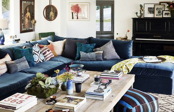 Throw Pillows - A living room with an oversized velvet sofa, mixed throw pillows and a rough-hewn coffee table
