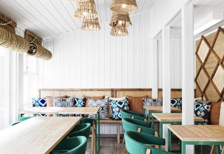 Pavimento in rovere scandinavo di Hackwood e pareti in legno dipinto di bianco per il luminoso locale Vino Veritas, disegnato da Masquespacio nel cuore di Oslo, in Norvegia. L'illuminazione è affidata a scenografiche lampade in rafia e corda
