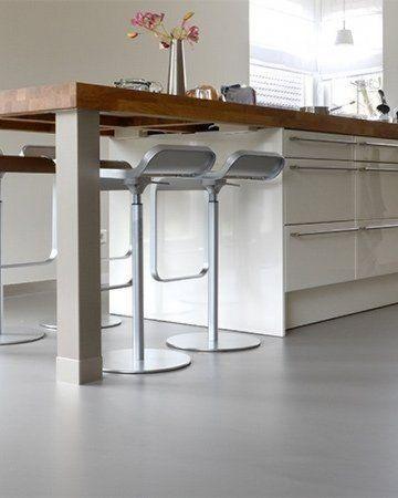 Lichtgrijze gietvloer met aluminum plint in keuken