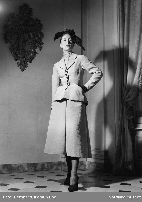 """La Ligne Corolle,""""The New Look."""" Modell i ljus dräkt med smal midja, betonade höfter och vid kjol. Dubbelradigt pärlhalsband, handskar, fascinator och pumps. Foto: Kerstin Bernhard, 1947"""