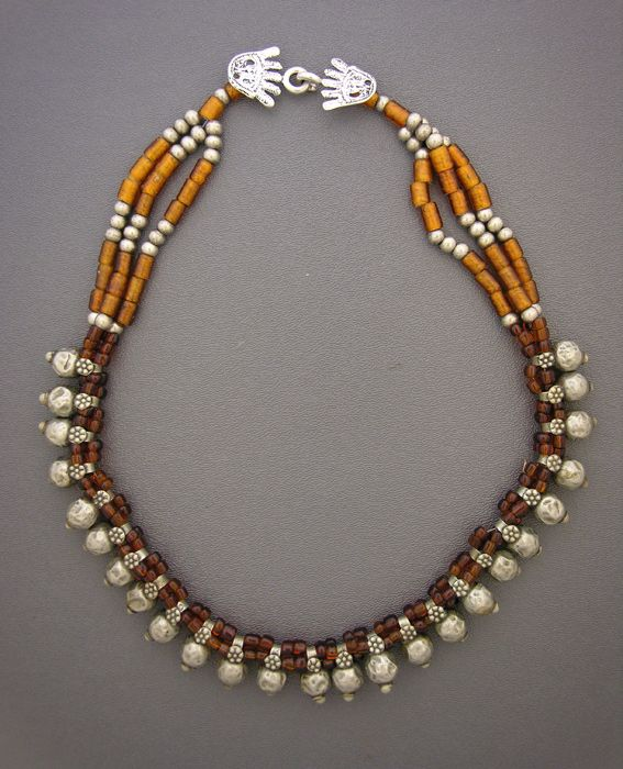 by Anna Holland | Twenty-five beautiful antique silver beads from Afghanistan, with brown and amber glass beads from Africa, round silver beads, and a sterling silver hamsa hook and eye clasp | 375$