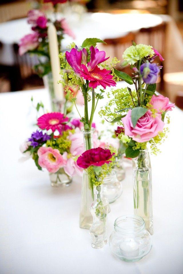 Versiering met veel verschillende vaasjes met bloemen! (en dan dus in de kleuren oranje, zalm roze, groen etc)