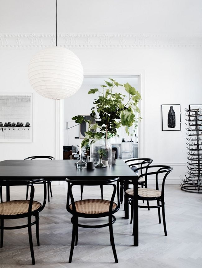 Minimalist dining area with a black table and paper lantern