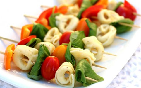 PASTA SALAD SKEWERS -- Serve your pasta salad on a stick to enhance the individual flavors of the salad. Large cooked noodles, like the tortellini shown here, are the perfect bite size. Add cherry or grape tomatoes, chopped peppers, and folded greens to complete the skewers. Be sure to mix everything in your favorite seasoning before assembling the skewers to get the full flavor of a pasta salad. Brilliant appetizer!