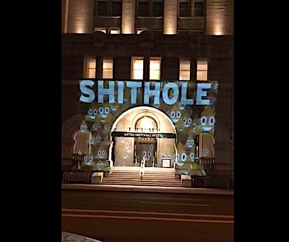 "1.12.18 Trump Hotel in downtown Washington DC got a surprise makeover last night—with the expletive President Donald Trump has used to describe developing world countries beamed onto its outer walls.  Video posted on Twitter shows the words ""This Place is a Shithole"" projected onto the walls of the hotel Saturday night, alongside poop emojis, and an arrow pointing at the establishment's arched entrance. (re: Haiti, Africa)"