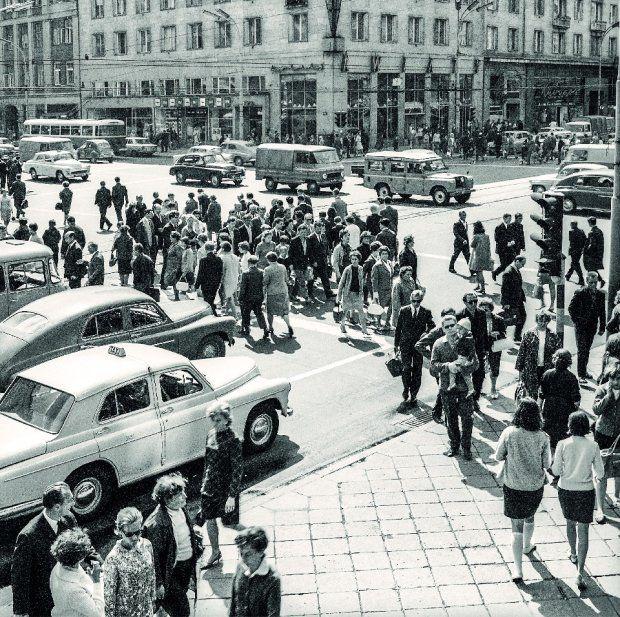 Skrzyżowanie Alej Jerozolimskich i ul. Kruczej należało w latach 60. do najbardziej ruchliwych w Warszawie. Tu zawsze coś się działo. Chodnikami przetaczały się tłumy ludzi. Ponad jezdnią widzimy rozpiętą trakcję. Tu bowiem linia tramwajowa przecinała się z trolejbusową (trolejbusy jeździły Kruczą).  Najpiękniej to miejsce wyglądało nocą, gdy ulicę rozświetlały wielkie witryny sklepów i efektowne neony. Szczególnie znakomity zdobił kwiaciarnię u zbiegu ulic. Znikła ona dopiero kilka lat…