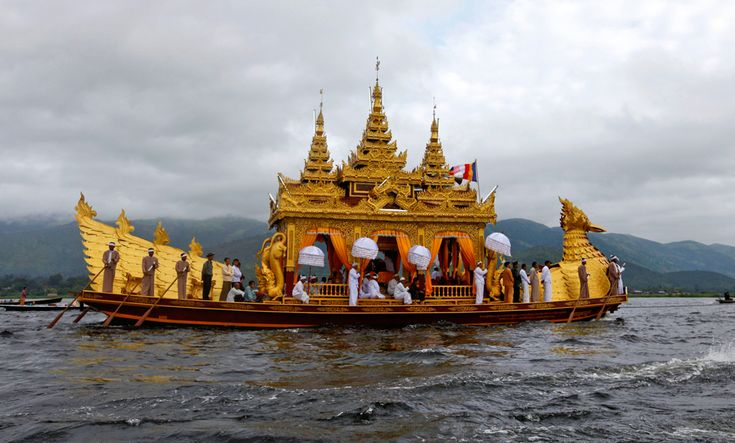 Locals stand on the Phaung Daw (Royal Boat) during the annual 18-day Phaung Daw Oo festival at Inle Lake, Myanmar. The boat houses five statues of Buddha gilded with gold leaf, which are believed to have been brought there by one of the kings of Bagan in the 11th century. Photo by Soe Zeya.