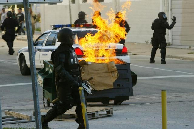 CAFTA: A trash fire, set by anti-FTAA protesters, burns as police in riot gear stand by on the fourth day of the summit to create a Free Trade Area of the Americas November 20, 2003 in Miami, Florida. Hundreds of protesters clashed with police. Protesters say the pact would damage the environment, exploit workers overseas and cost many Americans their jobs.