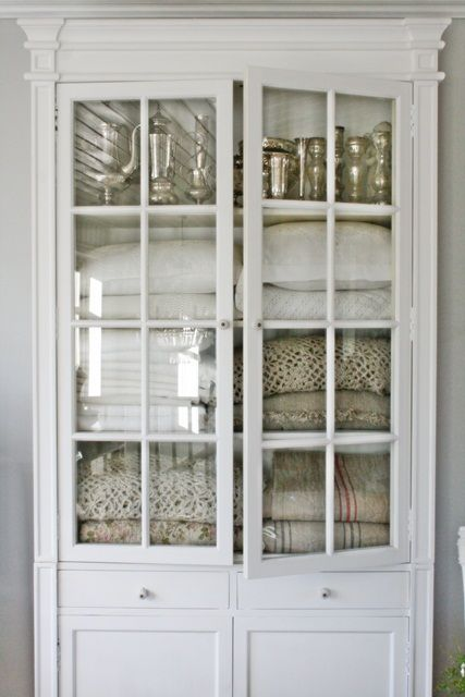 Vintage white cabinet with glass doors for linen storage.