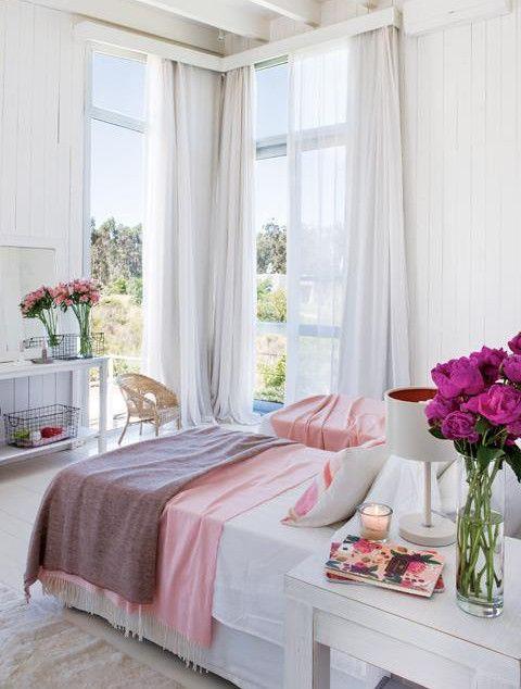 Спальня с высоким угловым окном и выходом на террасу. .