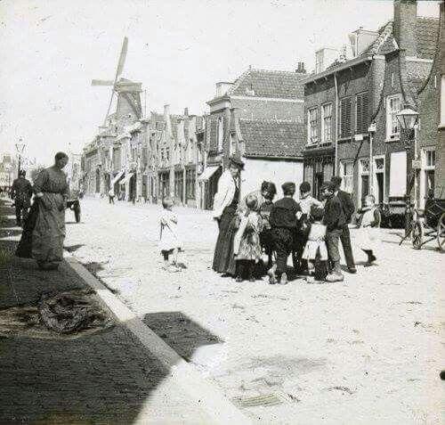 """Deze opname is van 1893 en toont het Broersveld, ter hoogte van het Herenpad. Het slootje/open riool is gedempt. De molen op de achtergrond is """"De Oost' (1727-1899), welke stond op het huidige Land van Belofte. Net links van """"De Oost"""" is dan net onttakelde molen """"De Witte"""" (1791-1893) te zien, die in hetzelfde jaar gesloopt zou worden. Schiedam"""