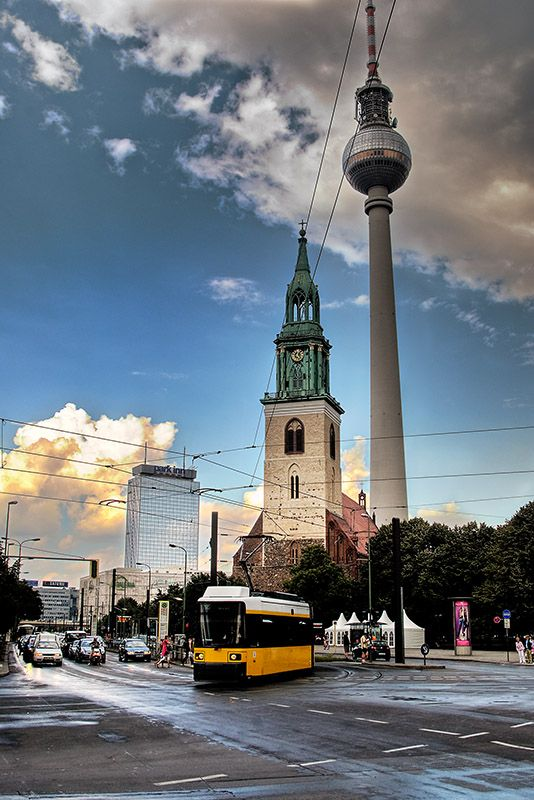 Berlin Alexanderplatz -A tram at sunset,with the Marienkirche and the TV tower at its back. Berlin, Germany