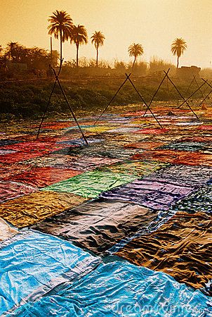 Colorful sari are dryed on the bank of river Yamuna near Agra in India. picture by Koscusko