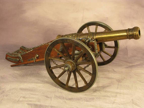 Superb Desk Ornament Vintage Model French Louise XIV Cannon Cast Metal and Wood  A beautiful vintage Desk ornamental piece in the form of a French Louise XIV cannon or field gun in accurate scale. 5 3/4 metal-rimmed rotating wheels, wood carriage and a 10 1/4 ornate barrel with brass patina and powder ladle & ramrod. Would look great on a study or office desk.  Dimensions: 18(45.7cm) long by 7 1/8(18cm) high Would make a fantastic gift
