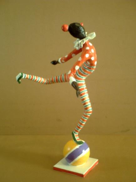 Escultura em papel de palhaço equilibrando-se sobre uma bola.