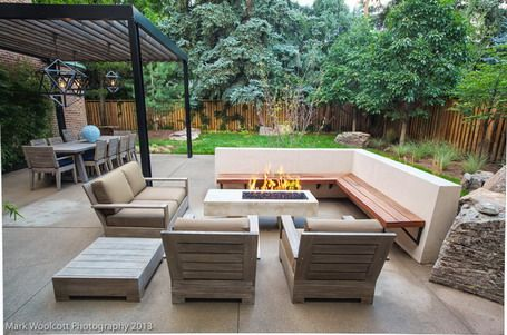 shaped wood decking seating and armchairs with cushions and gas fire