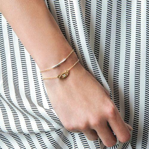 Bransoletka na ultracienkim łańcuszku z Okiem z kryształkiem Swarovskiego. Przy zapięciu zawieszka z logo zapobiegająca nadmiernemu przesuwaniu się bransoletki.  Wykonana w całości ze srebra próby 925 lub srebra pokrytego złotem.  Biżuteria pakowana jest w eleganckie pudełeczko ze specjalną wkładką zabezpieczającą srebro przed matowieniem.