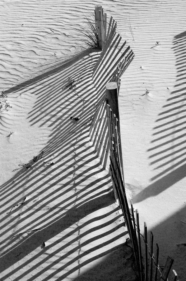 Sand and Sun - fence at the beach | photography black & white . Schwarz-Weiß-Fotografie . photographie noir et blanc | Photo: Robert Meanor |