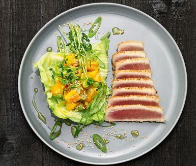 Sesamstekt tonfisk med en fräsch sallad gjord på avokado, mango, salladslök och lime. Ät gärna ihop med ris eller nudlar – toppa rätten med ärtskott.