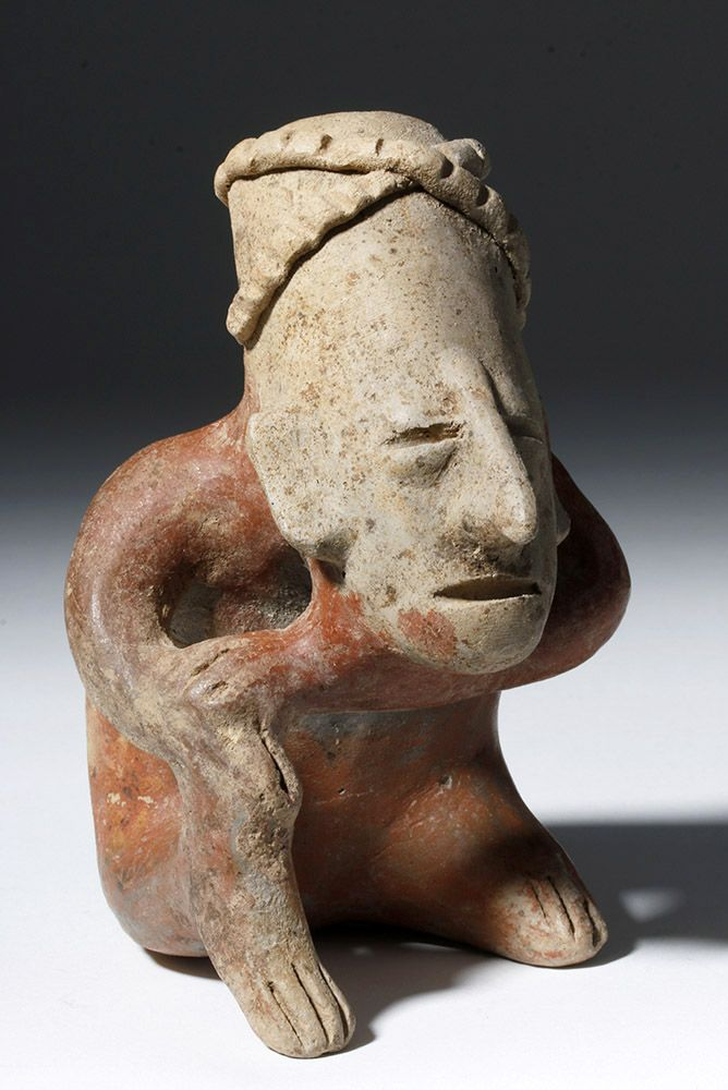 Pre-Columbian, West Mexico, Jalisco, San Juanito, ca. 200 BCE to 200 CE. A skillfully modeled bichrome pottery seated, perhaps hunchback figure posed with his left arm under his chin and left hand placed upon the wrist of his right hand which rests upon his right knee.  Possessing a characteristically elongated head, he presents a rather tranquil visage comprised of slit eyes and mouth, a long, protruding nose, and angular ears.  He wears a crossed headband of applied and incised coils, and…