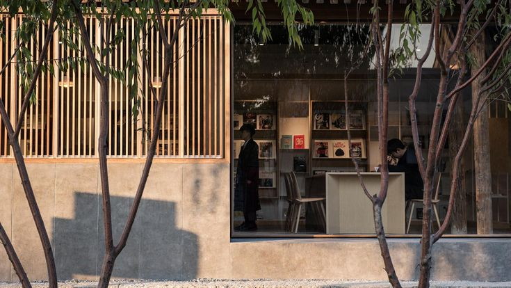 """Facing a picturesque canal amidst the cobblestoned """"hutong"""" alleyways in Beijing's old city, the poetically named Spring Whispers Book Club is a neighbourhood library occupying a typical one-storey cottage that has been thoroughly renovated by local architects Fon Studio."""