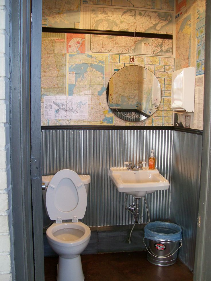 "I remodeled the bathrooms at our family business.  Since it is a gas station, I collected vintage gas station road maps & ""papered"" the walls with them.  Mirror was hung from black painted picture rail molding."