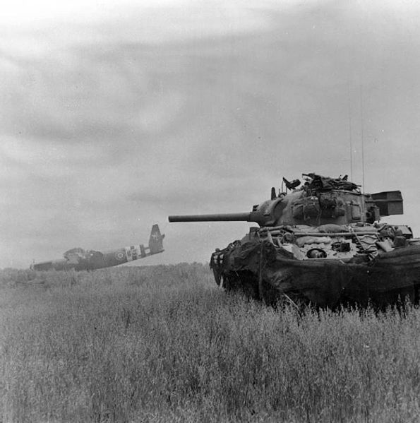 A Sherman tank of 13th/18th Royal Hussars in action against German troops using crashed Horsa gliders as cover near Ranville, 10 June 1944.