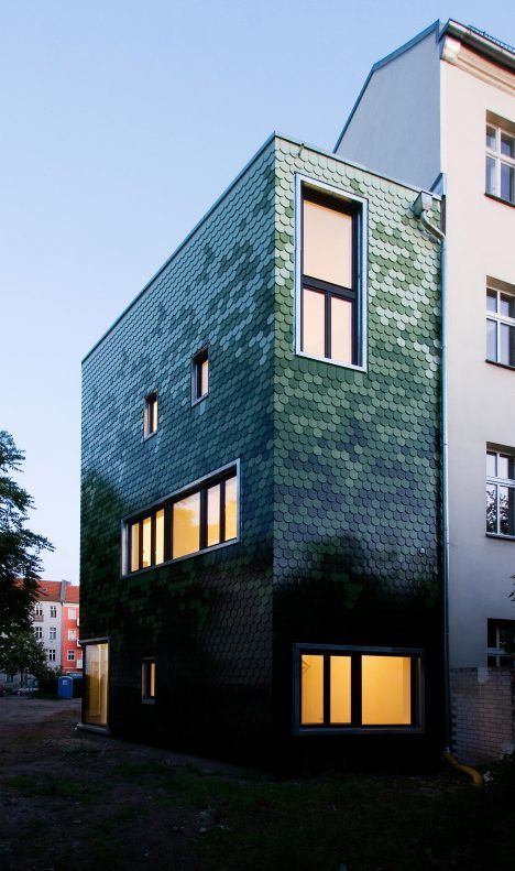 This house in Berlin designed by Brandt + Simon Architekten is covered in rows of green shingles with curved edges and features windows laid out to resemble a face