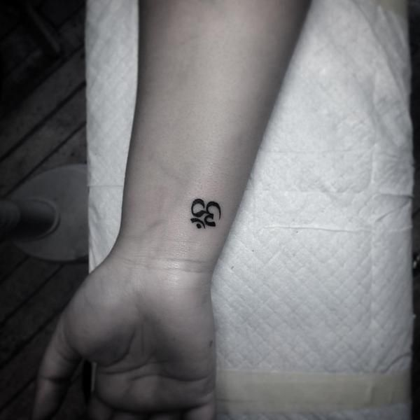 Hand poked Om tattoo on the wrist.