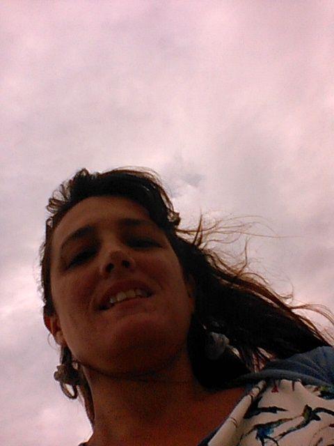 selfie toma contrapicada con nubes, los pelos en diagonal dirigen la mirada y dan movimiento, los pájaros de la remera revolotean hacia las nubes...
