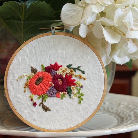 Hand embroidered on a 5 wooden hoop, these lovely flowers are stitched onto a white linen fabric.  Embroidery hoops look great as a standalone art piece hung on a wall or propped on a shelf. Each hoop is hand stitched by me and may have slight variations.  Feel free to contact me if youd like a custom hoop based on this pattern! I love doing custom orders.